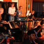 Jean-Luc au piano, Marianne debout, Arthur au clavier, Athis à la batterie. Au premier rang : Michael, Jamescy, Charlotte, Timothée et Sylvain